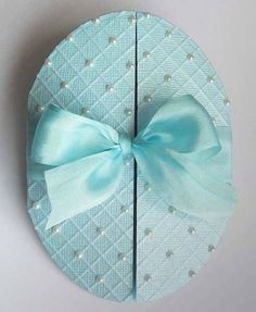 handmade Easter fold ... gatefold opening ... egg shaped ... embossing folder grid on shimmery blue paper with pearls on alternate crossings ... lovely big bow ...