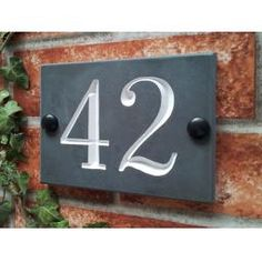 House number plaque in solid slate suitable for a two digit house number or one digit and a suffix.House number sign for two digit numbersSolid slate traditional product made in the UKDeep v-cut engravi. Slate House Numbers, Front Door Numbers, Door Number Sign, House Number Plaque, House Name Signs, Home Signs, House Names, Painted Slate, House Plaques