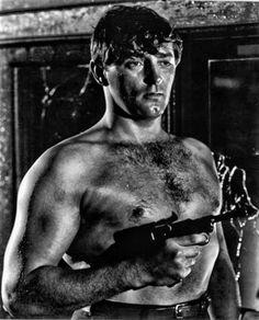 An oily Robert Mitchum handling his gun with pride.