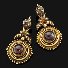 A pair of antique garnet pendent earrings, 1880s  Of Etruscan revival design, the central garnet cabochons set within a circular gold plaque of applied ropetwist and bead decoration, suspended from a gold surmount of similar detail, with hook fittings, mounted in 14 carat yellow gold, length 4.0cm