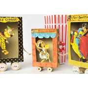 Recycle small food boxes (raisins, granola, pasta, etc.) by cutting the front panel out and adding 3D scenes (such as the circus theme shown). Can add matching-sized thread spools for wheels and connect w string.