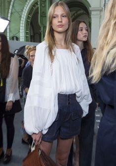 A voluminous blouse plus jeans shorts