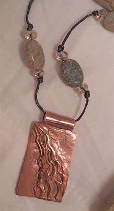 Rustic copper, hand-sculpted river pendant hung on fine leather cord and river jasper beads