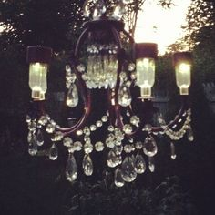 The solar chandelier lit up at night-Chandelier created by Valerie of Deco & Rust