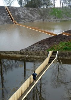 Sunken bridges made from a series of moats built over the West Brabant Water Line region of the Netherlands during the 17th century, to protect invasion from France and Spain.    Read more: Sunken Pedestrian Bridge in the Netherlands Parts Moat Waters Like Moses! RO & AD Moses Bridge – Inhabitat - Green Design Will Save the World