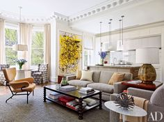Jonathan Browning Studios pendant lights are suspended over the kitchen island, adjacent to a Christopher Wool painting in a Boston townhouse decorated by Wells & Fox; the custom-made armchairs in the bay window are clad in a Claremont fabric.