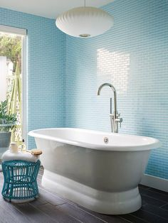 Walls of sky blue glass subway tiles give off the reflective qualities of water in this simple bathroom.
