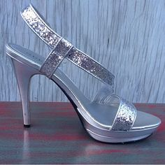 Stunning pair of glittered heels by Guess These show-stoppers are sexy and flashy, yet still classy and tasteful.  Paired with your favorite party dress, you'll be the star of the show.  Heel is 5.25 inches tall, and wider straps offer plenty of support.  Still in excellent condition - minuscule dents and lines on heels, sides, and soles, but only visible upon close inspection, and no loss of color anywhere, so they look new to everybody around you.  Silver with silver glitter.  Size 9…