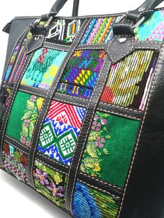 Our Multi Regions Black Tote features a playful yet one of a kind design. It has been carefully assembled with panels of beautiful and artistic huipil from different Guatemalan regions on both sides. Each regional huipil panel is separated by a leather strip which is designed to further emphasise the already brilliant and radiant colours of the huipil, while also giving it an elegant and classic style. It is a piece of art, outstanding in any environment! Black Tote, Handmade Design, Handmade Bags, Regional, Tote Bags, Classic Style, Clutches, Art Pieces, Environment