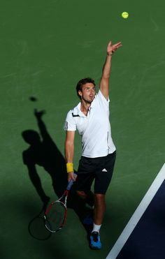 Ernests Gulbis Photos - Ernests Gulbis of Latvia serves to John Isner during the BNP Paribas Open at Indian Wells Tennis Garden on March 2014 in Indian Wells, California. Indian Wells Tennis, Bnp, Running, Sports, Photos, Racing, Hs Sports, Keep Running, Excercise