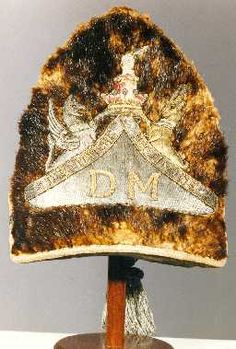 Officer's Grenadier Cap, Durham Militia, 1759-1761. Brown fur with an embroidered 'plate' on the front, made of silver wire with other coloured threads and the letters 'DM' and the crest of the Earl of Darlington, Colonel of the Regiment. On the back of the cap is a green velvet bag with a silver net and tassel. It belonged to Crosier Surtees of Redworth Hall near Newton Aycliffe. Born in 1739, he joined the Durham Militia when it was formed in 1759 and retired in 1761.