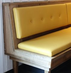 solid wood dining bench with upholstered seat and tufted back in yellow color