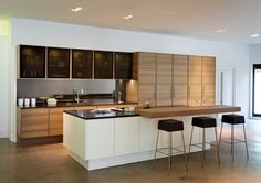 Great to bring wood tone to island.  Interesting contemporary take on glass fronts. Poggenpohl Kitchen Studio St. Albans