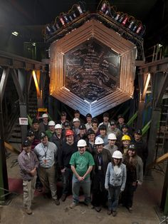 Scientists stand with the Minerva neutrino detector, located 330 feet underground at Fermi National Accelerator Laboratory