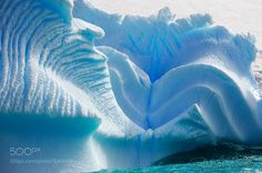 Iceberg in Antarctica carved by tides and tiny air bubbles.