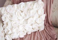 almofada de feltro 4 4) O próximo passo é enrolar o feltro, até que uma rosa seja formada. Assim que finalizar a rosa, passe uma linha com agulha na base, de uma extremidade a outra, e dê um ponto, para que ela fique presa.