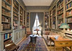 Love the room but GREAT carpet. Blue antique oriental rug, muted green library shelves with white trim in London townhouse.