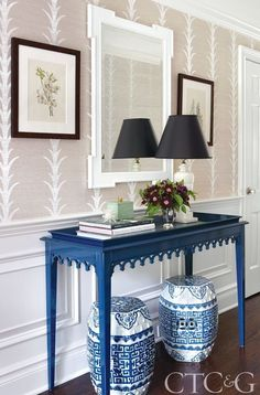 Connecticut Cottages and Gardens A console table from Oomph, Celerie Kemble acanthus striped wallpaper from Schumacher, and a pair of blue and white chinese garden stools in this stylish entryway.