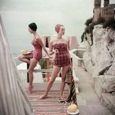 Two models overlooking water in Palermo wearing bathing suits, both of red, one plaid one checkered with shaggy elfin caps, 1955