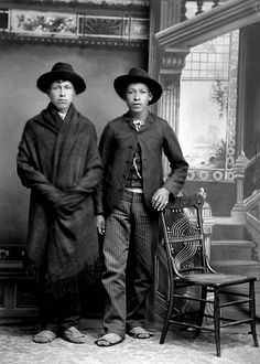 Ho-Chunk men. The man on the left, John Stacy (ChoNeKayHunKah), is wrapped with a blanket around his shoulders. The man on the right, Henry Greencrow (CooNooZeeKah), has his hand on a chair. Both men are wearing traditional Ho-Chunk moccasins. Photo: 1890.