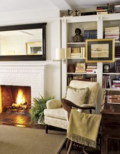 Painted brick fireplace flanked with shelves and large  mirror similar size to tv above real fireplace. Mantle would need to just be removed all together.