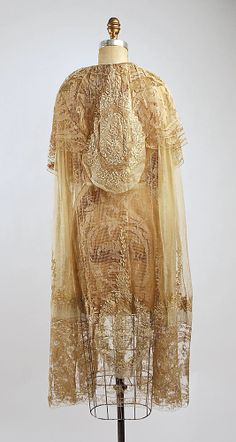 Evening ensemble (cape, rear view) Boué Soeurs (French) Date: 1918–20 Culture: French Medium: cotton, silk, metallic Dimensions: Length at CB (a): 50 1/4 in. (127.6 cm) Length at CB (b): 44 in. (111.8 cm) Credit Line: Bequest of Sally Fenlon-Young, 1979 Accession Number: 1979.129.2a, b
