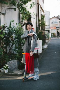 All smiles in a thick herringbone coat, grey marl sweatpants and Ne Balance 993 V3 sneakers! The red scarf is such a nice finishing touch!
