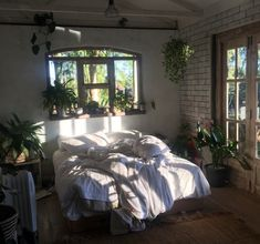 BAYLEY. Beautiful clean, bohemian bedroom with lush green plants and white bedding. white washed brick walls for a perfectly homey home.
