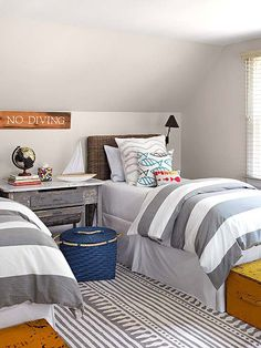 A mix of gray-and-white patterns comes together to form a youthful yet stylish kids' bedroom. Sunny yellow trunks at the end of each bed bring color to the room and add storage. The bright pops of color on the accessories and