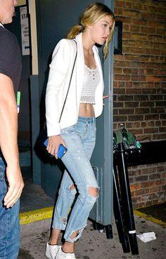 A modelo Gigi Hadid usa cropped top com blazer sobre os ombros.