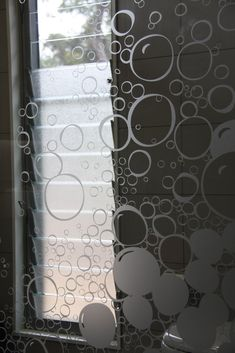 Custom designed soap bubble frosting to adorn architectural glass in bathroom.