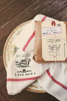 English-country-kitchen-inspired setting utilizes a printed dishcloth as a napkin, and presents the favor in a brown paper package designed to resemble old-style meat packaging.