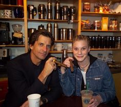 picture of Battlestar Galactica's original 1978 Lieutenant Starbuck (Dirk Benedict) with the 2004 series' Lieutenant/Captain Starbuck (Katee Sackhoff) at Starbucks drinking Starbucks