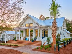 The exterior of a contemporary Lowcountry house, with white siding and a blue metal roof. Step inside!