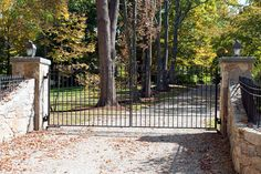 This driveway gate's straight lines are given a bit of visual interest with finials. Matching iron fence and swooping stone driveway walls. Modern Driveway, Stone Driveway, Wrought Iron Driveway Gates, Bedford Hills, Fencing Companies, Modern Entry, Tri State Area, Entry Gates, Homes