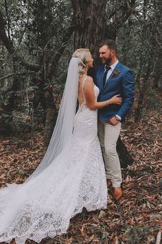 4c539082e3e74 Rustic country bride wearing lace dress with low back and catherdral veil.  Groom wearing blue