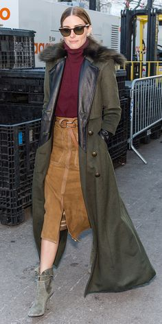 Olivia Palermo wearing a burgundy turtleneck, long military coat with fur collar, and suede midi skirt with slit
