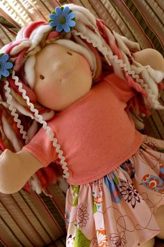 Love this Waldorf doll.  These dolls use products found in nature (cotton, wool, etc) and will have facial expressions that allow the child to imagine any expression they want the doll to have!  Thus, engaging the child into more imaginative, open-ended play.