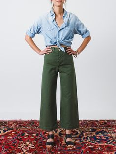 Ultra high-waisted, flared sailor pants in olive green dyed canvas with a contrast white button fly. These slightly cropped, structured trousers have two hidden front pockets at the waistband, belt lo