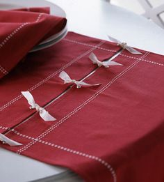 Festive Table RunnerRepurpose cloth napkins or place mats into a table runner. Add rivets to the edges of the linens. (Be sure to position the rivets evenly on each linen so the edges will match up.) Loop ribbon through the rivets and tie the linens together in a chain formation.