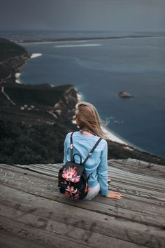 A woman with a backpack sitting on a wood surface while staring out into the ocean.