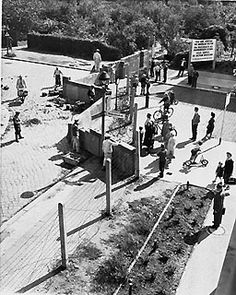 1961: the wall goes up  West Berliners watch East German construction workers erect a wall across Wildenbruchstrasse and Heidelbergerstrasse in West Berlin in August 1961. Built with barbed wire and concrete, The Berlin Wall, stretching for about 30 miles, becomes a Cold War symbol separating East and West Berlin, preventing people from leaving East Germany. (AP Photo)