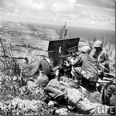 American soldiers firing the 37mm gun. U.S. Marines shelling Japanese soldiers from the 37-mm anti-tank gun from the position at the top of Mount Tapochau.