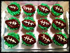 Footballs on grass. Green grass is made with a star tip. Melt ghiradelli chocolate in a double boiler and pipe into football shapes. Melt ghiradelli white chocolate and pipe laces after footballs cool.