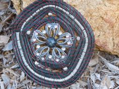 Pine Needle Basket Black Sun Catcher Ornament w/ Silver Vintage Laced Flower Center 5 x 4 1/4 approx. Oval black pine needles handmade with a Vintage Silver Laced Flower Center, accented with a black get center and 5 silver beads then tied with Maroonish / Brown Waxed Irish Linen string. Also, wrapped in some areas with silver wire. All baskets, ornaments and sun catchers are one of a kind and handcrafted... Needles are gathered and washed by hand. Some are dyed, this proces...