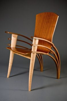 The Trimerous chair is a custom chair made to your size and height. The triple walnut arms are each 4 tapered laminations, the front legs are carved out of solid curly maple and the seat is vacuum formed from 19 layers of veneer.
