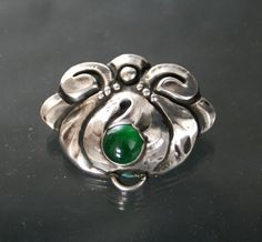 """Knud Georg Jensen. Skonvirke silver and green stone brooch; attached pendant dangle missing. Marks KGJ, 830S and D - Hammer - A"""" for Dansk Arbedje, trade association for promoting Danish product. Solid.View 1."""
