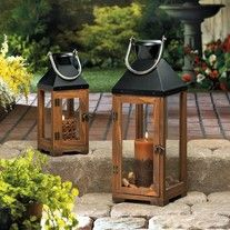 """The harmony of elegant wood and sleek black metal makes this tall candle lantern a designers dream come true. The clear glass panels let candlelight shine brightly and the oversized stainless steel hanging loop is the perfect finishing touch.   23 1/4"""" high with handle.   Candle not included...."""