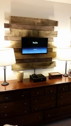 Pallet tv holder  We used 2 large beams on the back. Offset pieces horizontally. Choose to stain or not stain. We chose to sand, stain, and distress. Drill hole large enough for cables to go through the back. Use flatscreen flat hanging system to mount to wood. Mount wood to wall with French cleat hanging system, heavy duty. Cost was less than $10 since we already had the tv with mount.
