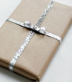 Brown paper package tied up in silver glitter ribbon